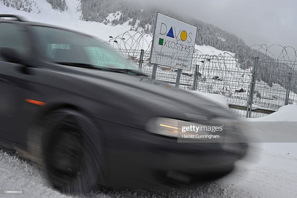 Car passes a Davos sign displayed behind barbed wire at the village entrance on January 10, 2012 in Davos, Switzerland. The World Economic Forum, which gathers world top leaders will take place from January 25, 2012 to the 29th.