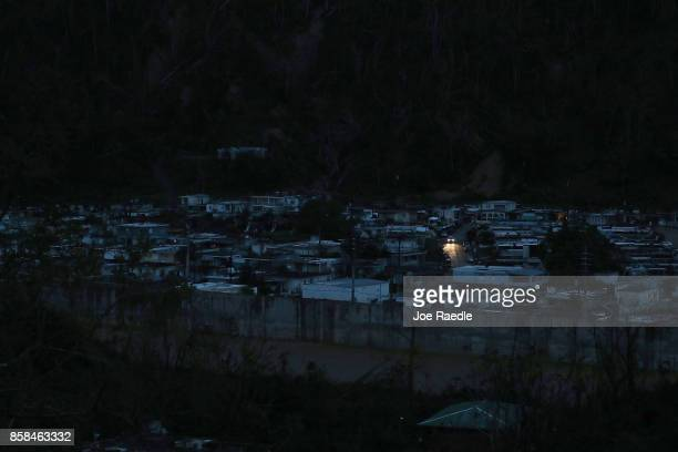 A car passes among dark homes as people wait for electricity to be restored after Hurricane Maria passed through on October 6 2017 in Utuado Puerto...