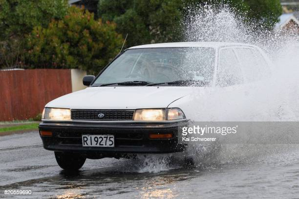 A car passes as rising waters cause flooding in Bay View Road in the suburb of Moncks Bay on July 22 2017 in Christchurch New Zealand Heavy rain...