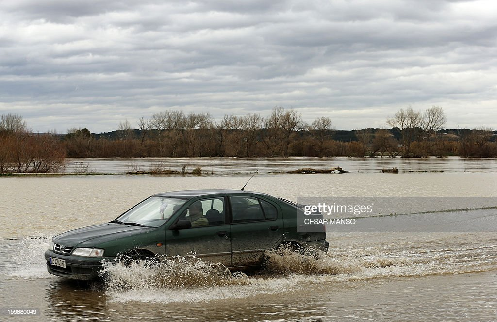 A car passes on a flooded road following the rise of the River Ebro, due to heavy rainfall, in Novillas, near Zaragoza, on January 22, 2013. AFP PHOTO / CESAR MANSO