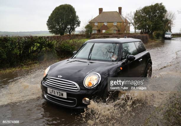 A car passes through a flooded road in Alfriston East Sussex as more heavy rain sweeps across the country