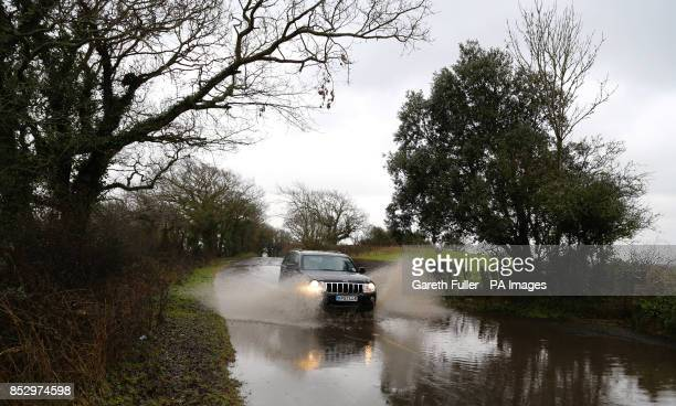 A car passes through a flooded road in Hooe East Sussex as more heavy rain sweeps across the country