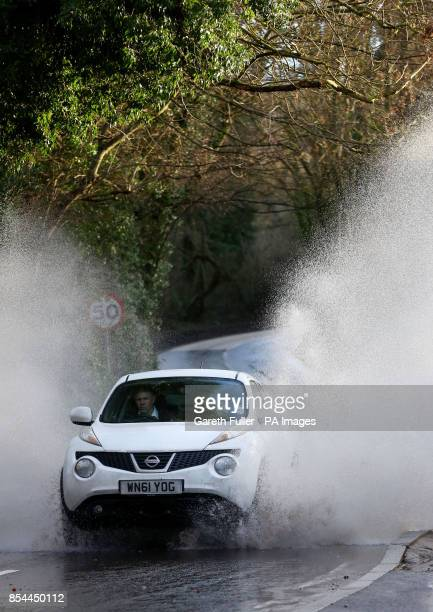 A car passes through a flooded road near Yalding Kent as more heavy rain sweeps across the country Picture date Monday December 30 2013 See PA story...