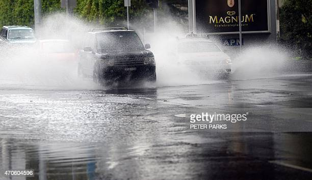Car passes through floodwater on a street in Sydney as the city battles cyclonic wind gusts and nonstop downpours on April 22 2015 Heavy rain and...