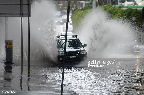 A car passes through floodwater on a street in Sydney as the city battles cyclonic wind gusts and nonstop downpours on April 22 2015 Heavy rain and...