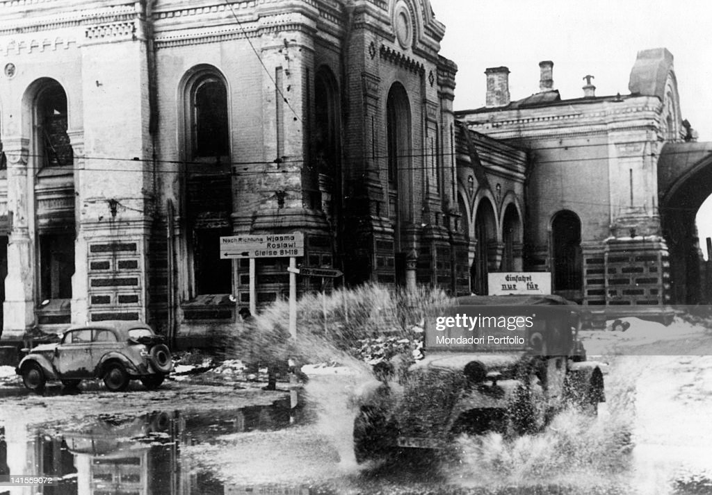 A car passing through the station square flooded by the thaw Smolensk April 1942