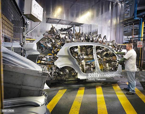 Car Plant Worker Assembling Car