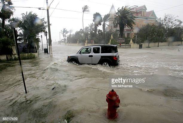 A car plows through a flooded street near the Southernmost Point in Key West after heavy rains generated by Hurricane Dennis slammed the island July...