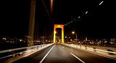 Car point of view of crossing the Rainbow Bridge at night. Tokyo Prefecture, Japan