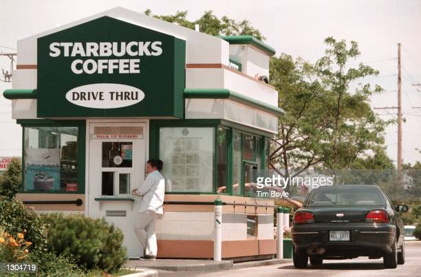 A car pulls up to a dualwindow standalone walkup and drivethrough Starbucks Coffee shop June 23 2000 in Lombard IL This driveup shop is the first of...