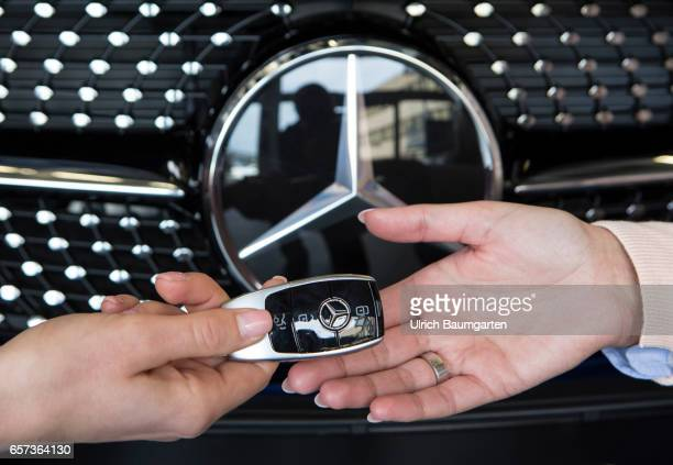 Car purchase the symbol photo shows the hand of a seller with a Mercedes Benz car key and the hand of a buyer during the vehicle handover in front of...
