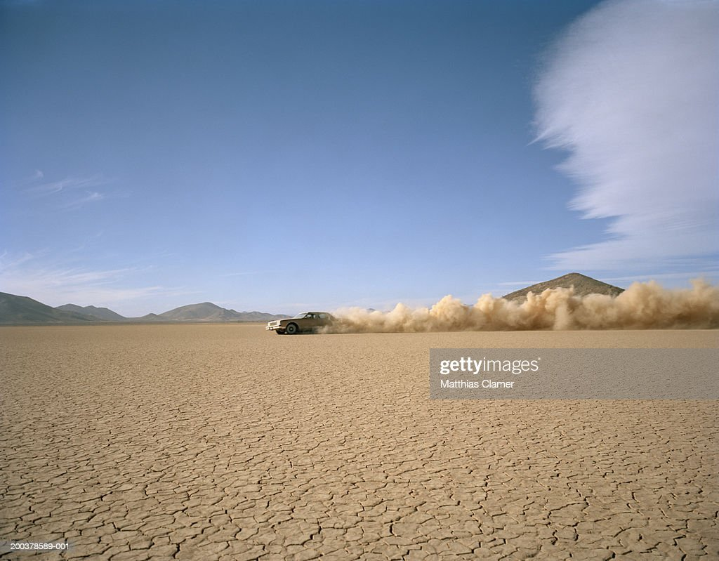 Car racing through desert, side view : Stock Photo