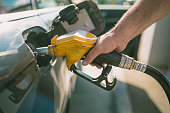 Car refueling on petrol station. Man pumping gasoline oil. This photo can be used for automotive industry or transportation concept