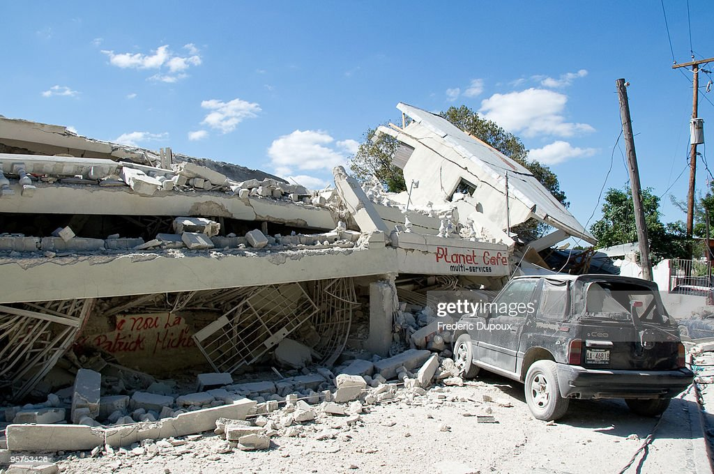 A car remains parked outside the ruins of a cafe January 13 2010 in PortauPrince Haiti Planeloads of rescuers and relief supplies headed to Haiti as...