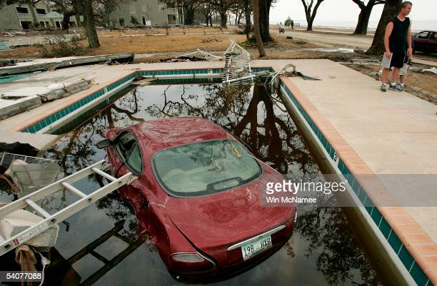 A car rests partially submerged in a swimming pool outside an apartment building destroyed by Hurricane Katrina September 1 2005 in Biloxi...