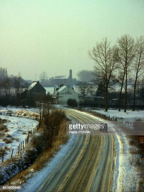 Car rolling on snowy road in the country circa 1980 in France