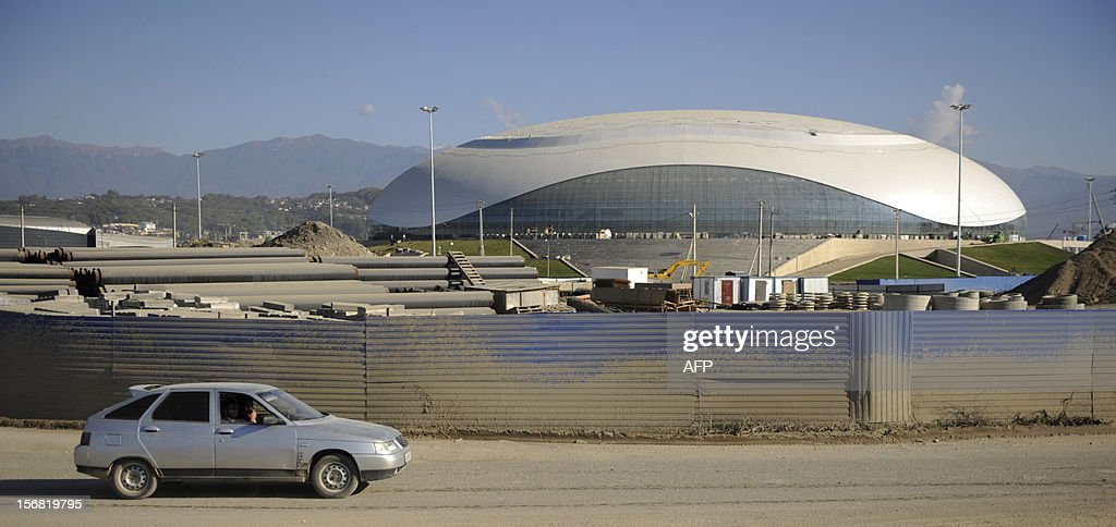 A car rolls near the Bolshoi Ice Palace construction site at the Olympic Park in the Russian Black Sea resort of Sochi, on November 22, 2012. Sochi will host the 2014 Winter Olympics. The Olympic Park will be able to accommodate about 75000 visitors when full, and all the ice arenas will be within walking distance of one other. AFP PHOTO / MIKHAIL MORDASOV