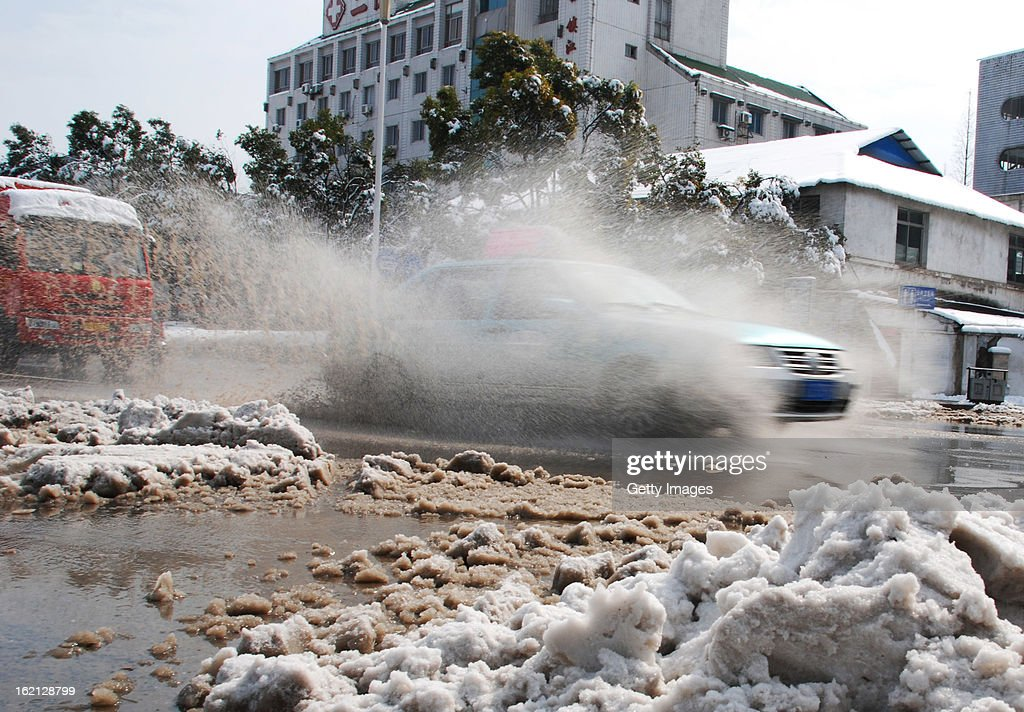 A car runs along a snow-covered road on February 19, 2013 in Zhenjiang, China. Heavy snow hit large areas of east China on Tuesday.