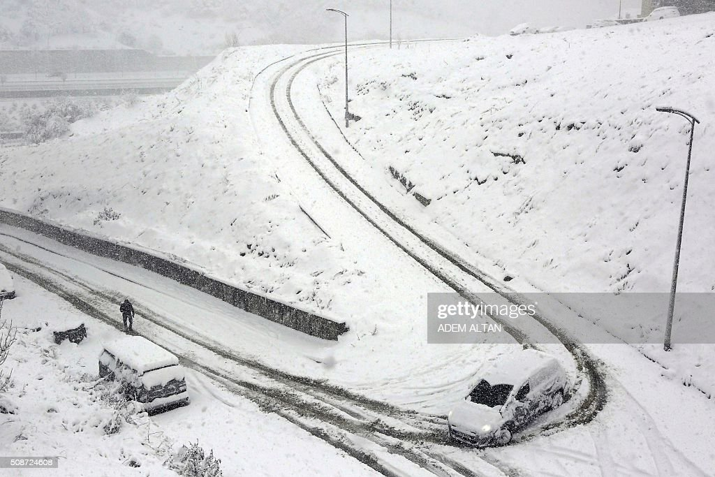 A car runs down the hill as a man walks by under the snow in Ankara on February 6, 2016. / AFP / ADEM ALTAN
