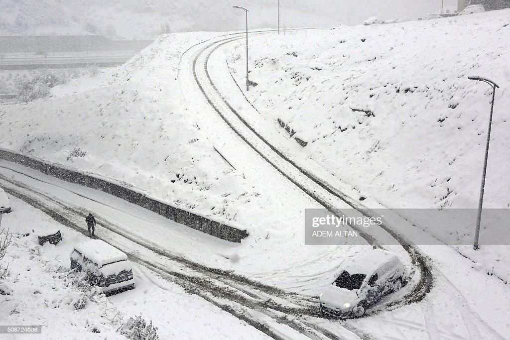 A car runs down the hill as a man walks by under the snow in Ankara on February 6, 2016. / AFP / ADEM ALTAN