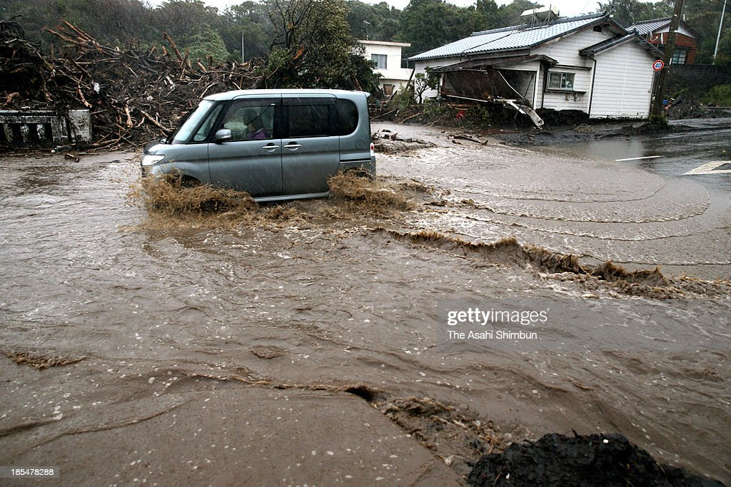 A car runs on the flooded road on October 20, 2013 in Oshima, Tokyo, Japan. The evacuation advisory was issued October 19 as another heavy rain was expected at a landslide devastated Oshima Island. The early morning downpours from Typhoon Wipha, or No. 26 on October 16 caused landslides that covered 1.14 million square meters and damaged or destroyed 283 homes, according to estimates by Oshima town officials.