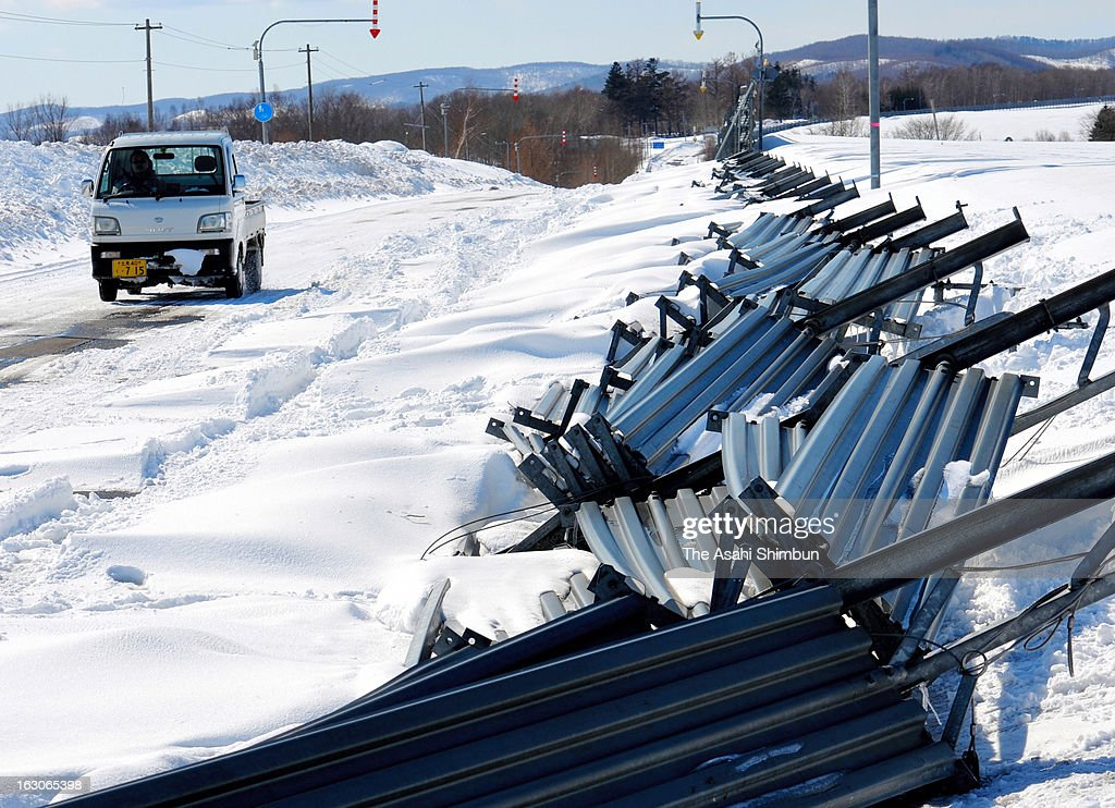 A car runs snow a snow-covered road which snow fence were broken by blizzard on March 4, 2013 in Abashiri, Hokkaido, Japan. The death toll rises to nine after a 76-year-old woman found frozen dead.