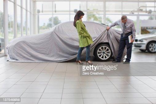 Car salesman displaying car for woman