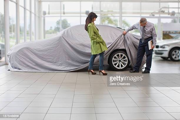 Car salesman displaying car for woman