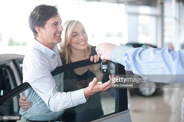 Car salesman handing key to couple in showroom