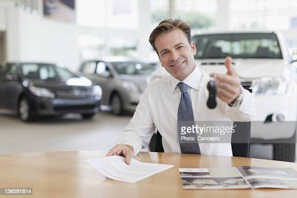 Car salesman handing keys over desk