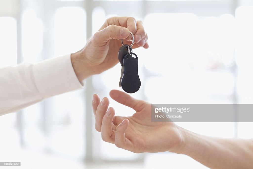 Car salesman handing keys to customer : Stock Photo