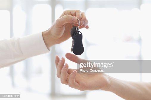 Car salesman handing keys to customer : Stock Photo
