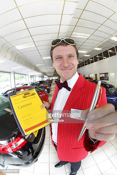 Car salesman holding pen and contract