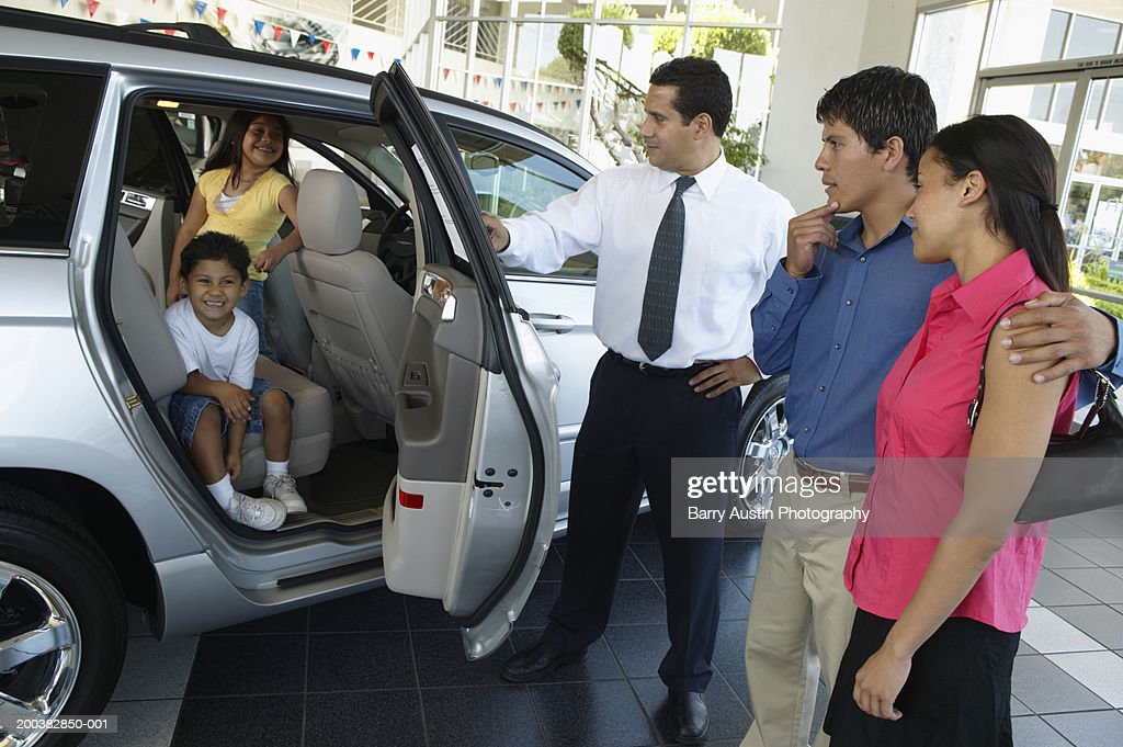 Car salesman showing car to family in showroom, children inside SUV : Stock Photo
