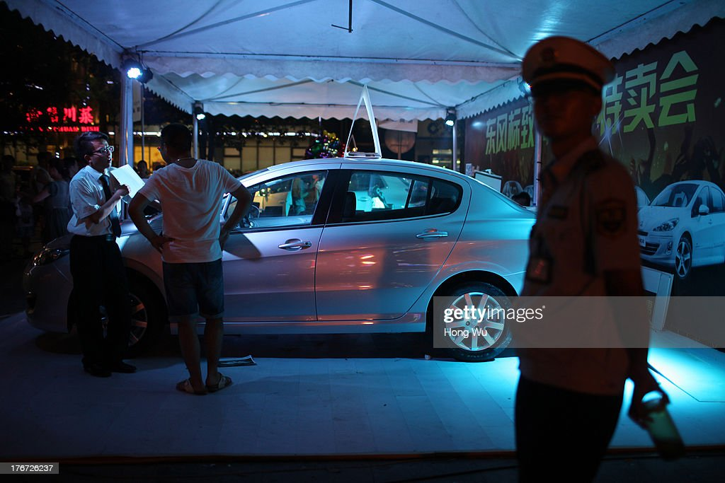 A car salesman spruiks a new car as a security guard watched on in the night on August 4, 2013 in Chongqing, China. Chongqing is a major city in southwest China and became the municipality was created on 14 March 1997. It known as a 'Mountain City' and 'River City' was constructed on the mountain and along the Yangtze River.