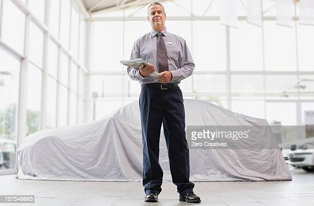 Car salesman standing in showroom