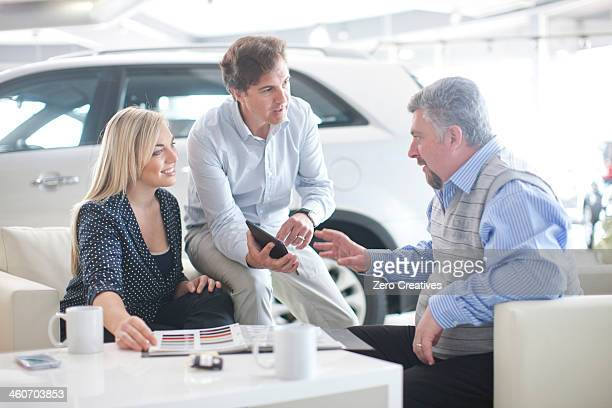 Car salesman talking to couple in car showroom