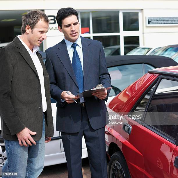 Car salesman talking with customer outdoors