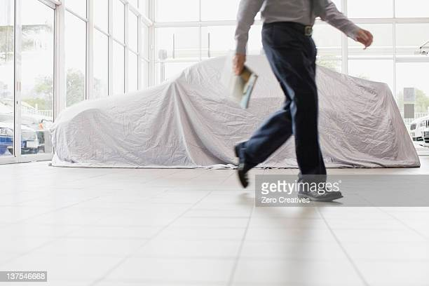 Car salesman walking in showroom