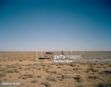 Car salesman with car smiling in desert, portrait : Stock Photo