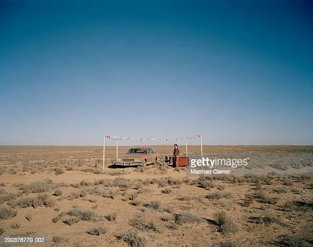 Car salesman with car smiling in desert, portrait