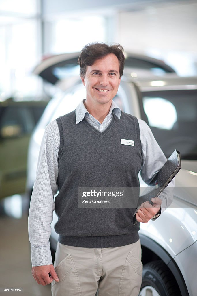 Car salesman with file in showroom