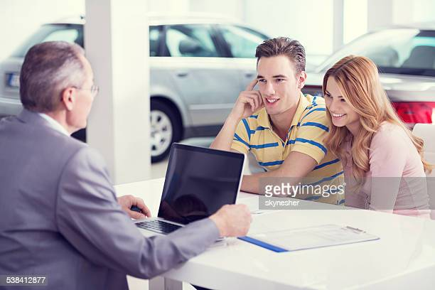 Car salesperson talking with young couple.