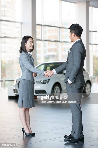 Car saleswoman talking with customer