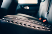 Detail of a stitch of an elegant car seats upholstered in black handmade leather. Side view