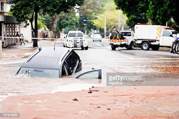 Car sinks into pothole in flooded urban road