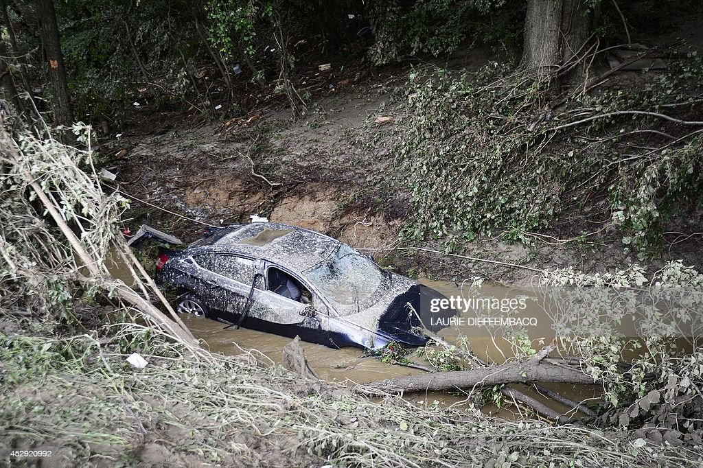 A car sits in mud after heavy rainfall led to flooding in Ittre in the Belgian province of Walloon Brabant on July 30, 2014.
