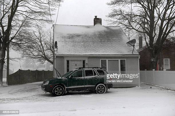 A car sits in the driveway of a snow swept home during a snowstorm on North Street March 26 2014 in Hyannis Massachusetts An early spring storm...