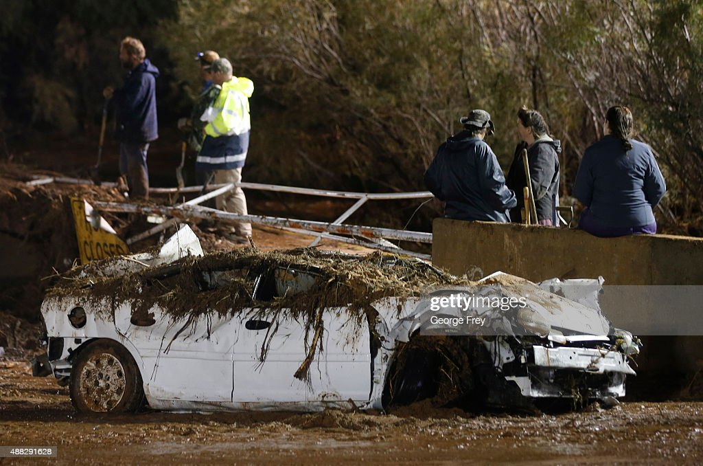 A car sits on the side of the road after being pulled from Short Creek as woman and rescuers watch large construction equipment remove flood debris...