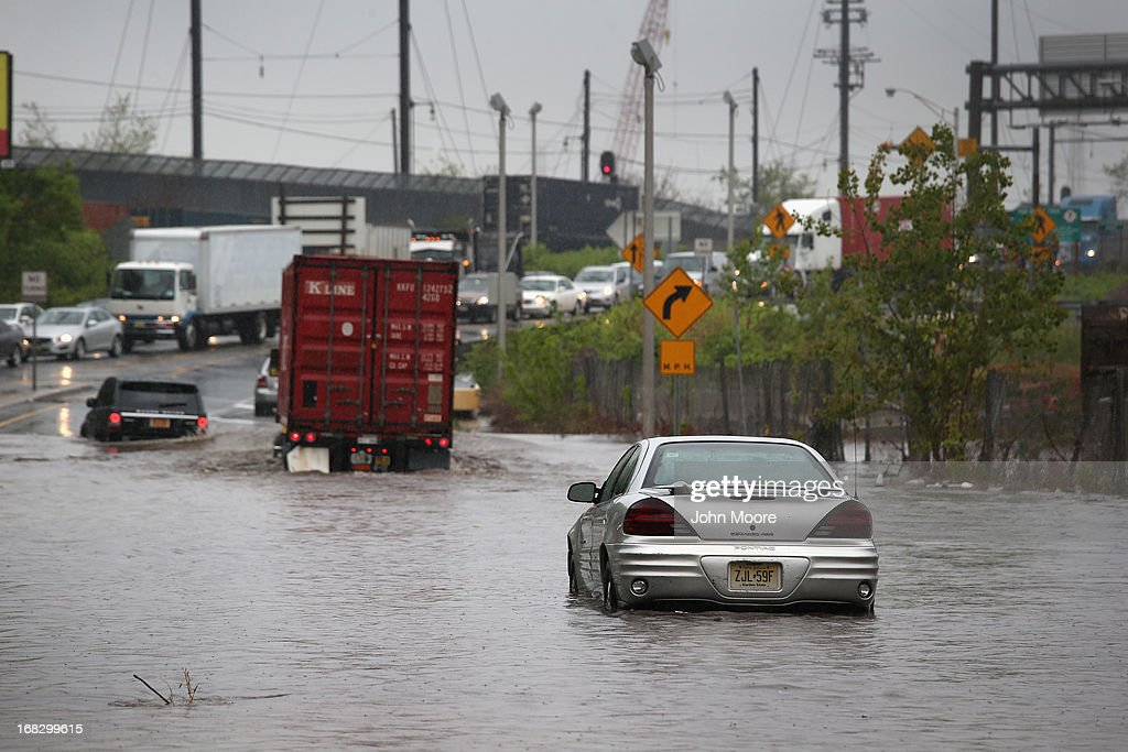 A car sits stranded in floodwaters on May 8, 2013 in Jersey City, New Jersey. Heavy rains flooded streets, stranding some motorists during morning rush hour traffic.